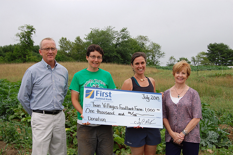 Gathered at the farm for a check presentation are (from left) Tony McKim, president and CEO of First National Bank; Sara Cawthon, farm manager at Twin Villages Foodbank Farm; Megan Taft, farm development at Twin Villages Foodbank Farm; and Susan Norton, eecutive vice president and chief administrative officer at First National Bank.