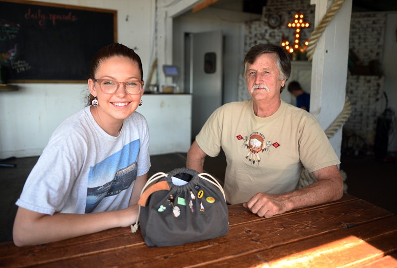 McKinley Neuser sits at The Contented Sole with Carl Reilly Sr., who found and returned her purse after it fell off of her scooter Monday, July 30. (Jessica Picard photo)