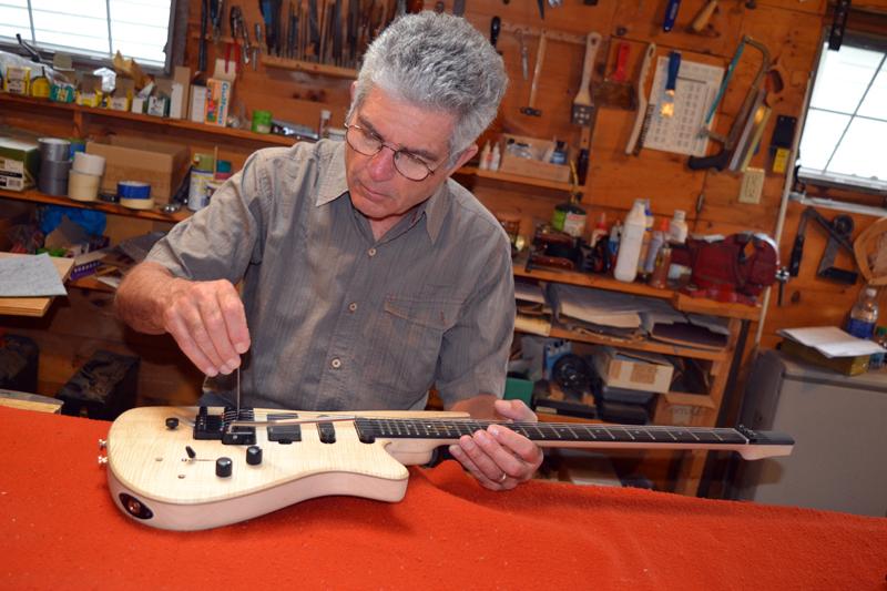 Ned Steinberger adjusts the bridge on a guitar in his Nobleboro workshop. (Christine LaPado-Breglia photo)