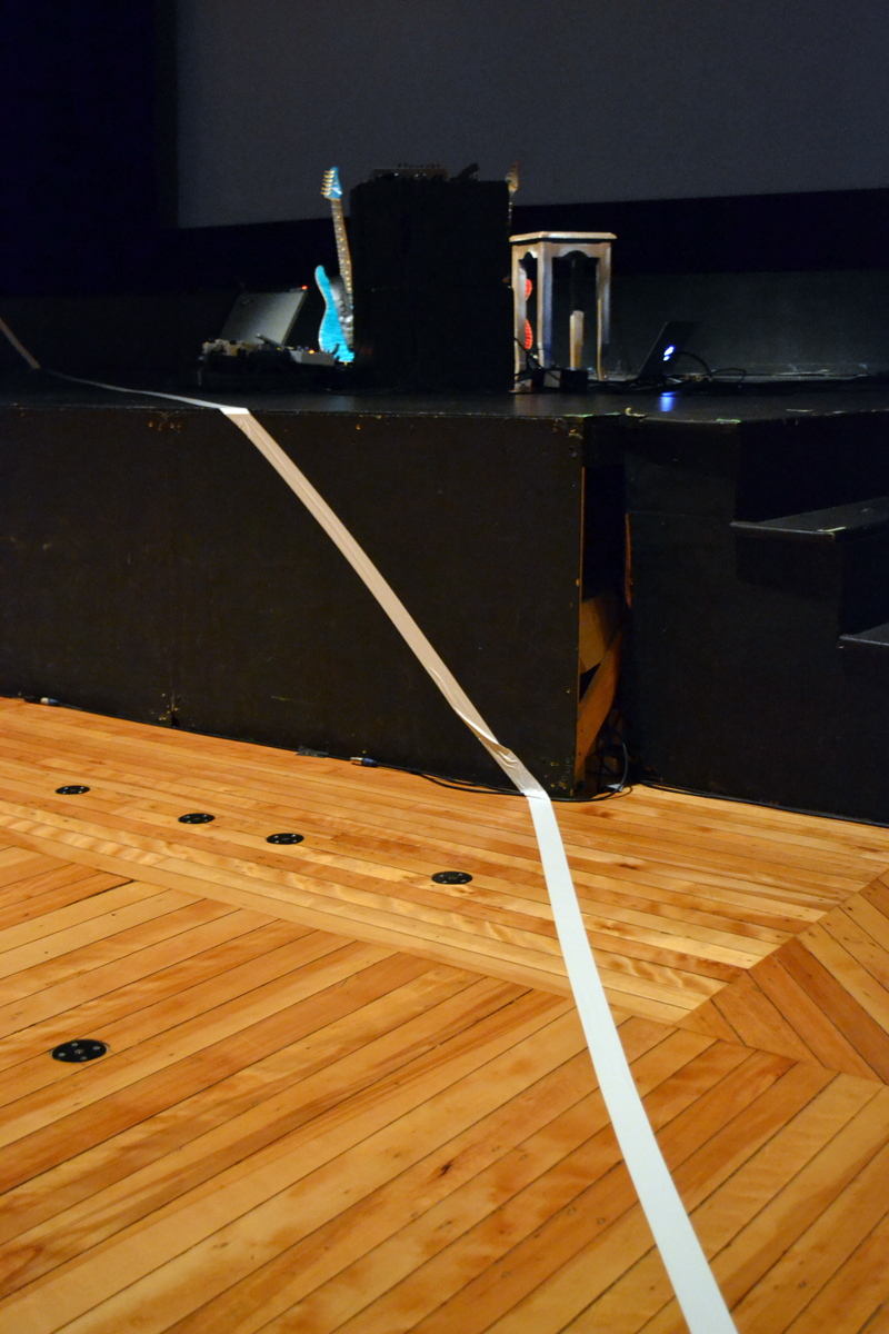 "A boundary line made of wide white tape separating avant-garde musician-composer Steven Mackey from his audience echoes the white boundary line featured repeatedly in the film portion of his multimedia presentation of ""Orpheus Unsung"" at Lincoln Theater. (Christine LaPado-Breglia photo)"