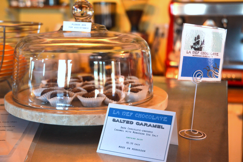 "A display case of La Nef Chocolate candies in The Barnacle Cafe. The card describes the candies as ""dark chocolate-enrobed caramel with Monhegan Sea Salt."" (Maia Zewert photo)"