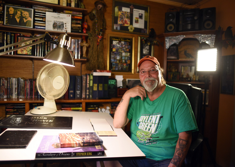 Artist Glenn Chadbourne sits in his home office in Newcastle, surrounded by books he has illustrated, including many by famed horror author Stephen King. (Jessica Picard photo)