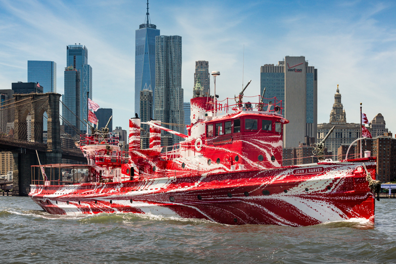 "The John J. Harvey with the New York City skyline in the background. A seasonal resident of South Bristol owns the historic fireboat. Its temporary paint job mimics the ""dazzle"" camouflage of World War I. (Photo courtesy Public Art Fund)"
