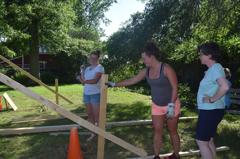 From left: Hannah Leitzell, Clara Brown, and Michelle Brand work on the new outdoor classroom at Wiscasset Elementary School. (Jessica Clifford photo)