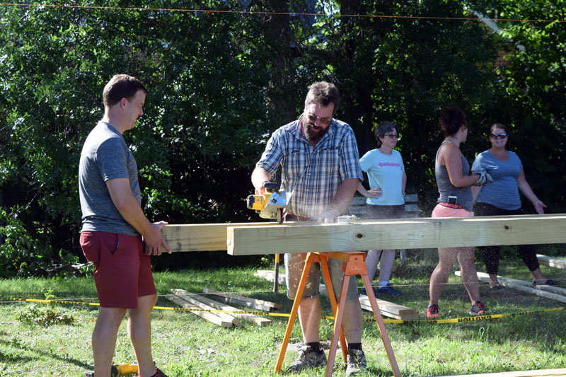 Charles Leitzell (left) and Jason Putnam work together to saw a beam for a new outdoor classroom at Wiscasset Elementary School. (Jessica Clifford photo)