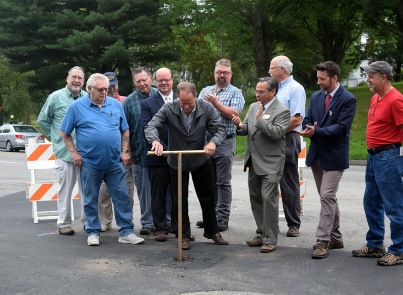 Wiscasset Water District Board of Trustees Chair Gregg Wood turns a valve to commemorate the completion of an 11-year project to replace about 35,000 feet of pipe more than a century old. (Jessica Clifford photo)
