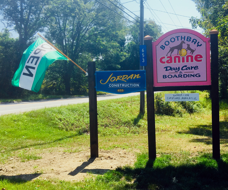 The pretty pink sign for Boothbay Canine Day Care & Boarding on Route 27. (Suzi Thayer photo)
