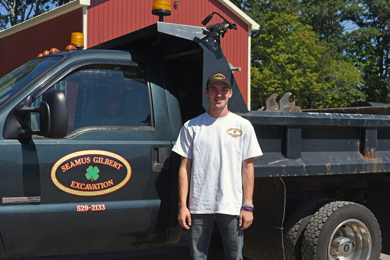 Seamus Gilbert, 18, stands next his dump truck at his office in Nobleboro, Tuesday, Sept. 4. (Jessica Picard photo)