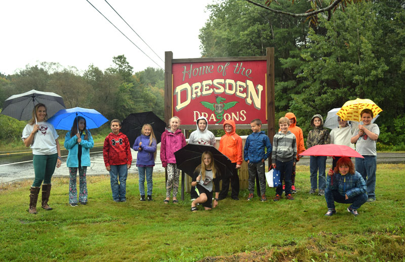 Katrina Willey poses with Dresden Elementary School fifth-graders and some fourth-graders by the school's new sign on a rainy Tuesday, Sept. 11. (Jessica Clifford photo)