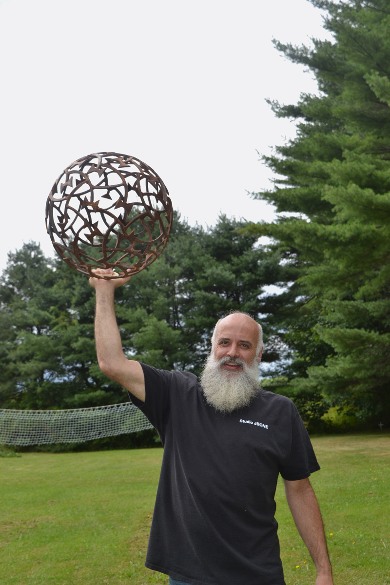 "Metal artist Jay Sawyer poses with ""Constellation I"" on the grounds of Studio JBone in Warren. (Christine LaPado-Breglia photo)"