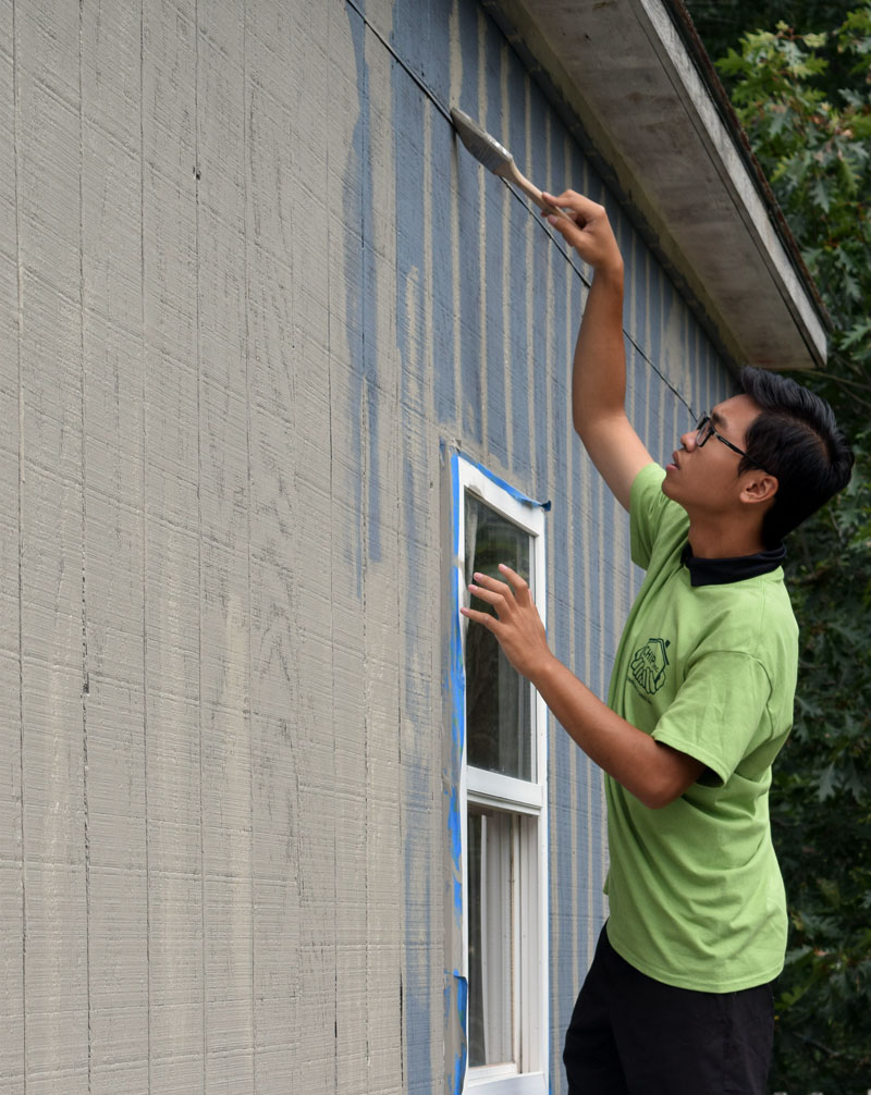 Lincoln Academy senior William Doan paints Shannon Bailey's garage. (Jessica Clifford photo)