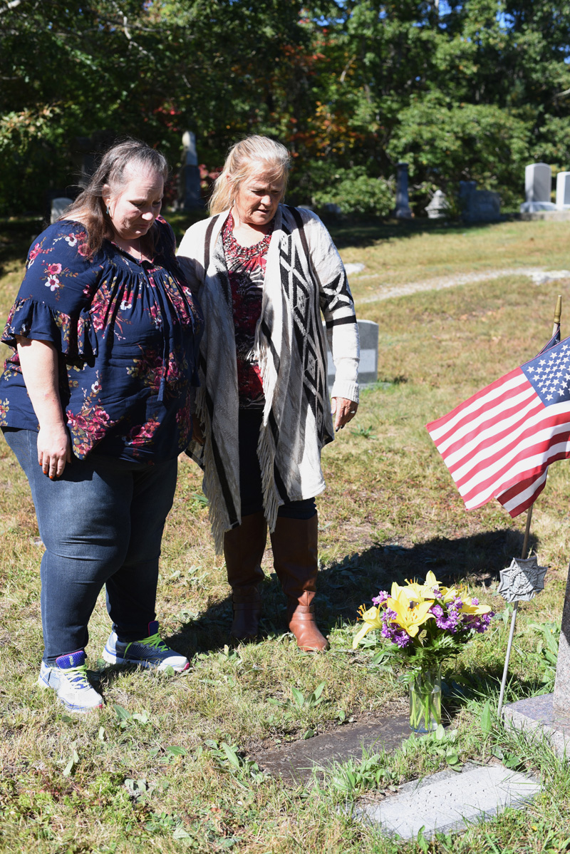 "Sisters Carolyn Mattern (left) and Liz Michaud visit the grave of their late brother, Sheldon ""Skip"" Cushing, in the Chamberlain Cemetery in Round Pond on Oct. 5. (Jessica Picard photo)"