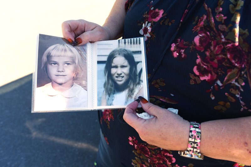 Carolyn Mattern holds photos of her sister, Liz Michaud, left, and herself as children. (Jessica Picard photo)
