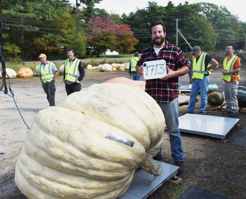 Alex Noel, of Connecticut, poses with his first-place 1,713-pound giant pumpkin during the Damariscotta Pumpkinfest weigh-off at Pinkham's Plantation in Damariscotta, Sunday, Sept. 30. (Jessica Picard photo)