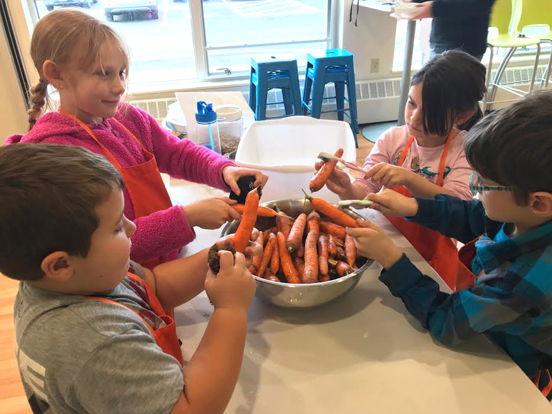 GSB second-graders clean carrots at FARMS Kitchen.