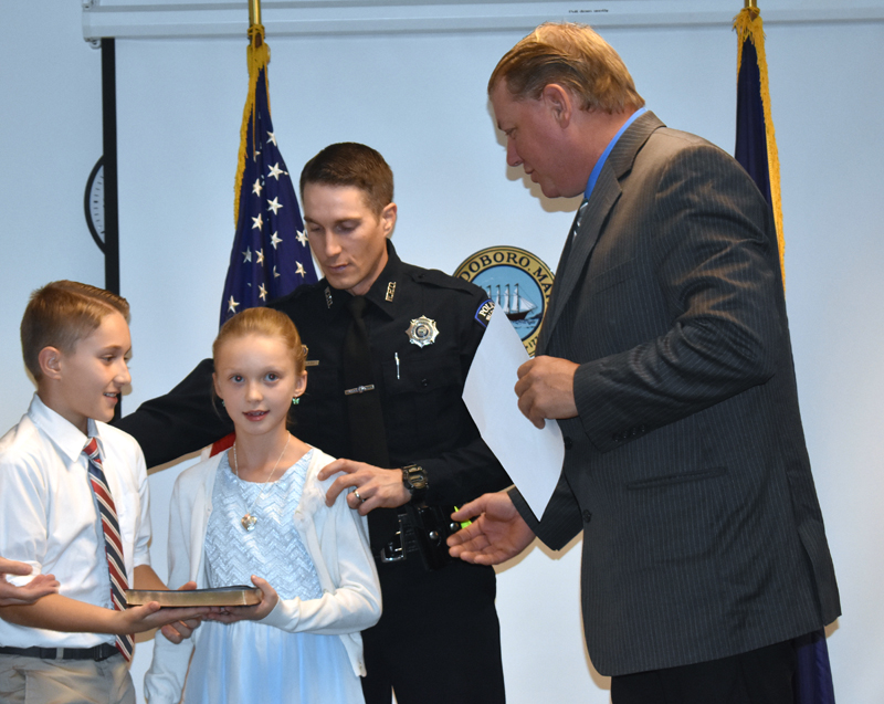 Waldoboro Selectman Abden Simmons (right) prepares to swear in John Lash as Waldoboro's police chief as Lash's children assist. (Alexander Violo photo)