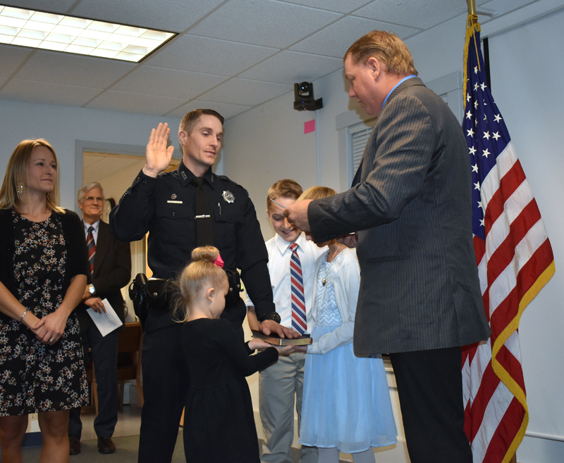 Waldoboro Selectman Abden Simmons (right) administers the oath of office to Police Chief John Lash as Lash's children hold the Bible and his wife looks on. (Alexander Violo photo)