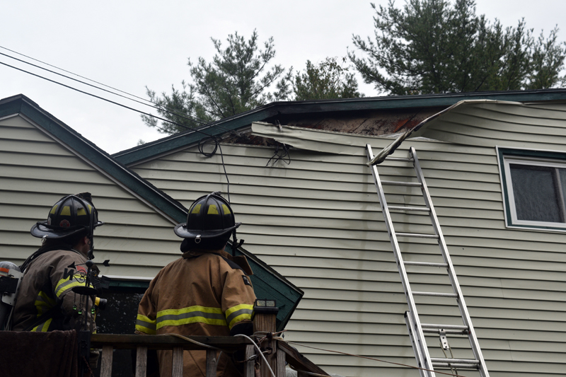Firefighters examine damage to the siding of a home on Cooper Road in Whitefield after extinguishing an electrical fire the afternoon of Monday, Oct. 1. There were no injuries as a result of the fire. (Jessica Clifford photo)