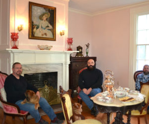 The new owners of the former Musical Wonder House in Wiscasset relax in the music room with their dogs. From left: Dana Long, Michael Collins, and Dan Dyer. (Charlotte Boynton photo)