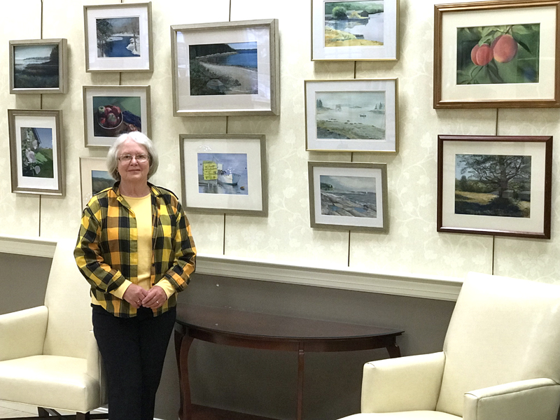 Kay Hannah stands before a wall of her artwork.