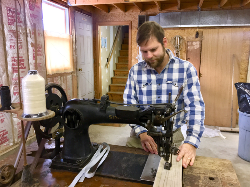Mike Bartles works at a 19th-century Singer 7 Class sewing machine in his new sail loft in Boothbay. (Suzi Thayer photo)