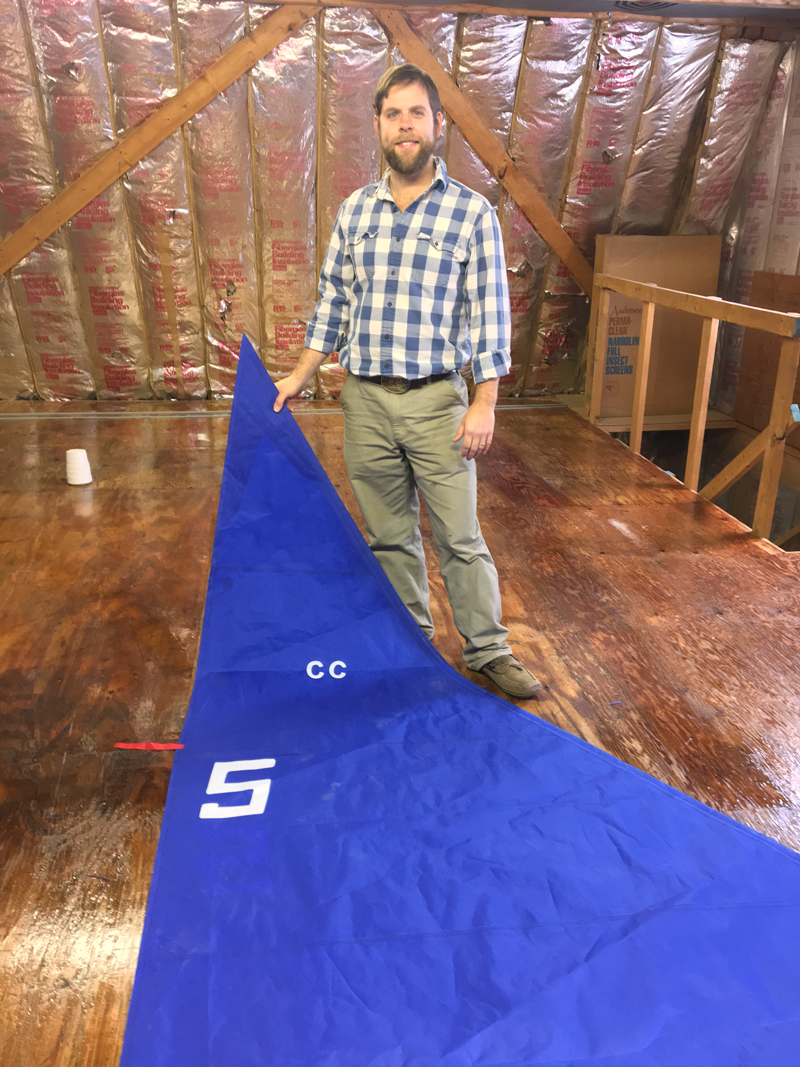 Mike Bartles poses with a recent project, a small blue sail for a dinghy, in his new sail loft in Boothbay. (Suzi Thayer photo)
