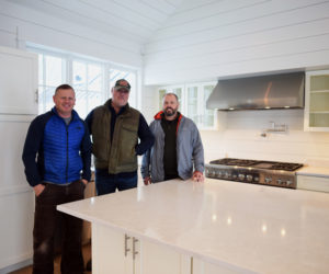 From left: contractor Paul Leeman III, developer Xavier Cervera, and architect Tor Glendinning stand in the kitchen of Cervera's new house in Round Pond, Monday, Nov. 26. (Jessica Picard photo)