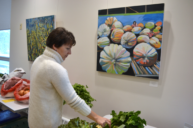 "Susan Bartlett Rice's paintings ""Maize"" (left) and ""Amongst the Giants"" serve as a backdrop as Central Lincoln County YMCA Membership and Marketing Director Leslie Gomes chooses a bunch of celery from the Morning Dew Farm table at the Y on Friday, Nov. 16. (Christine LaPado-Breglia photo)"