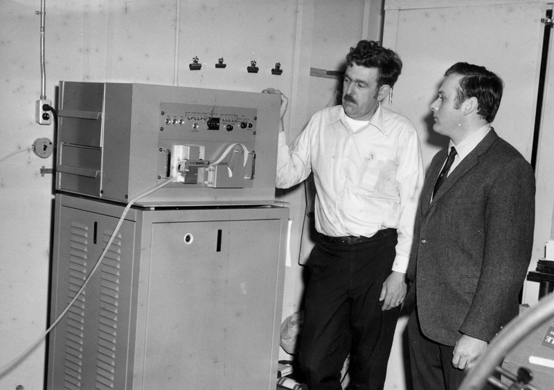 Sam Roberts (left) examines a Compugraphic typesetting terminal after its installation at The Lincoln County News circa 1969. The system was the first of its kind in the state.