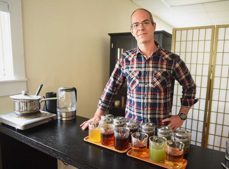 Joshua Jacobs, president of Samovar Tea, stands with a sampling of teas in the business's new tasting room in downtown Newcastle, Friday, Nov. 9. (Jessica Picard photo)