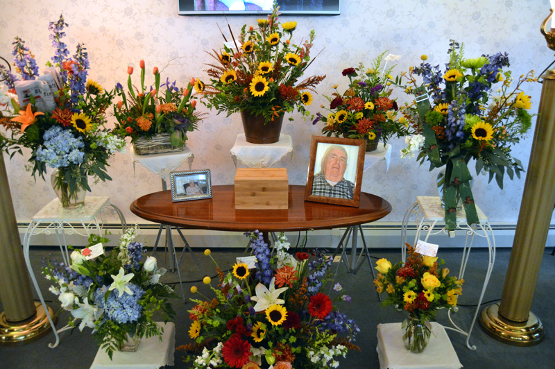 """A display of flowers and photos in memory of Samuel E. """"Sam"""" Roberts, publisher emeritus of The Lincoln County News, at the Strong-Hancock Funeral Home in Damariscotta on Thursday, Nov. 15. The bouquet at left holds the Nov. 8 edition of the newspaper, the bouquet at right a pair of his trademark suspenders. (J.W. Oliver photo)"""