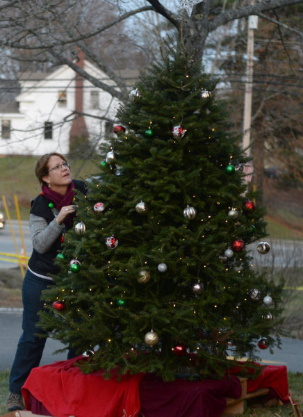 Mary Kate Reny puts the finishing touches on the tree by the Second Congregational Church in Newcastle during the 2017 Villages of Light event. (Paula Roberts photo, LCN file)