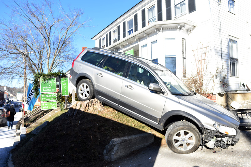 A station wagon at rest on a stump in the front yard of Crissy's Breakfast & Coffee Bar in Damariscotta on Thursday, Dec. 13. The car struck the building while backing up. (Jessica Picard photo)