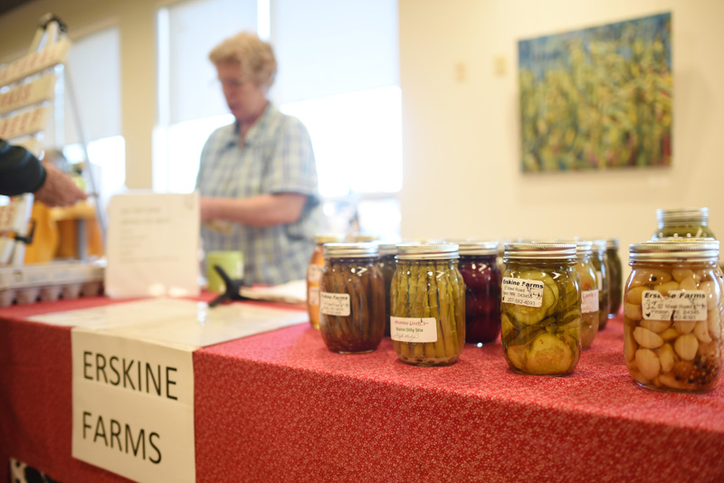 Jars of asparagus, pickles, and other goods are displayed on the Erskine Farms table as Iris Erskine helps a customer at the indoor farmers market at the CLC YMCA in Damariscotta, Friday, Nov. 30. (Jessica Picard photo)