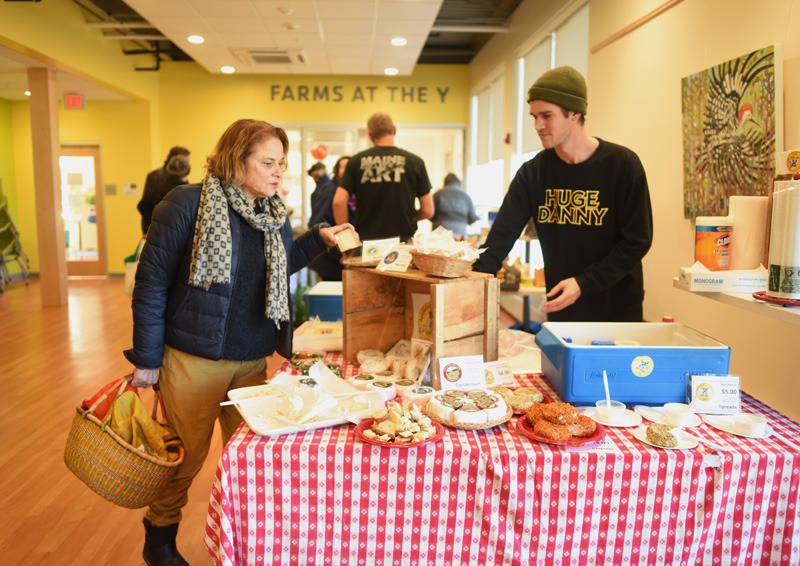 Daria White, of Damariscotta, looks at cheese from Appleton Creamery as employee George Hill mans the creamery's table at the farmers market at the CLC YMCA in Damariscotta, Friday, Nov. 30. (Jessica Picard photo)