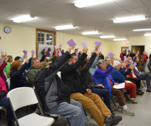 Dresden voters raise their cards to approve the purchase of a 1994 ladder truck during a special town meeting at Pownalborough Hall on Monday, Dec. 10. (Jessica Clifford photo)