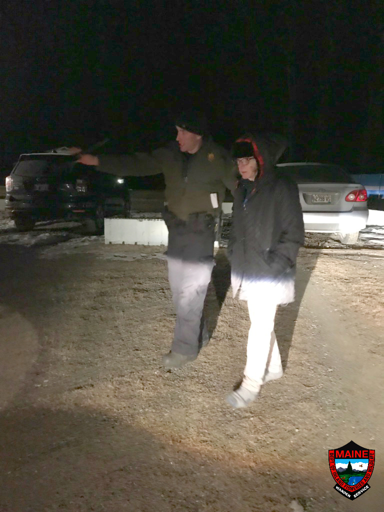 Game Warden Chris Roy walks with Darlene Bell, 66, of Whitefield. A search by game wardens and state troopers located Bell in woods about a quarter-mile from her home on Gardiner Road. (Photo courtesy Maine Warden Service)