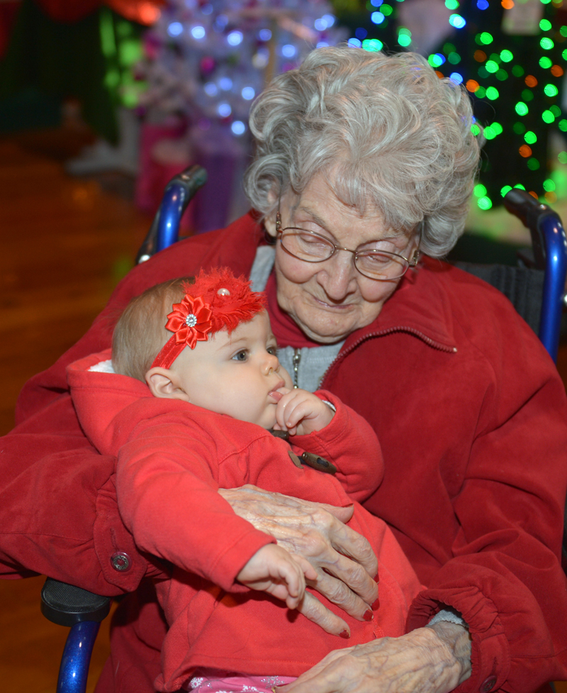 St. Andrews Village resident Louise Greene holds 8-month-old McKayla Taylor at the Festival of Trees at the Boothbay Harbor Opera House. (Paula Roberts photo)