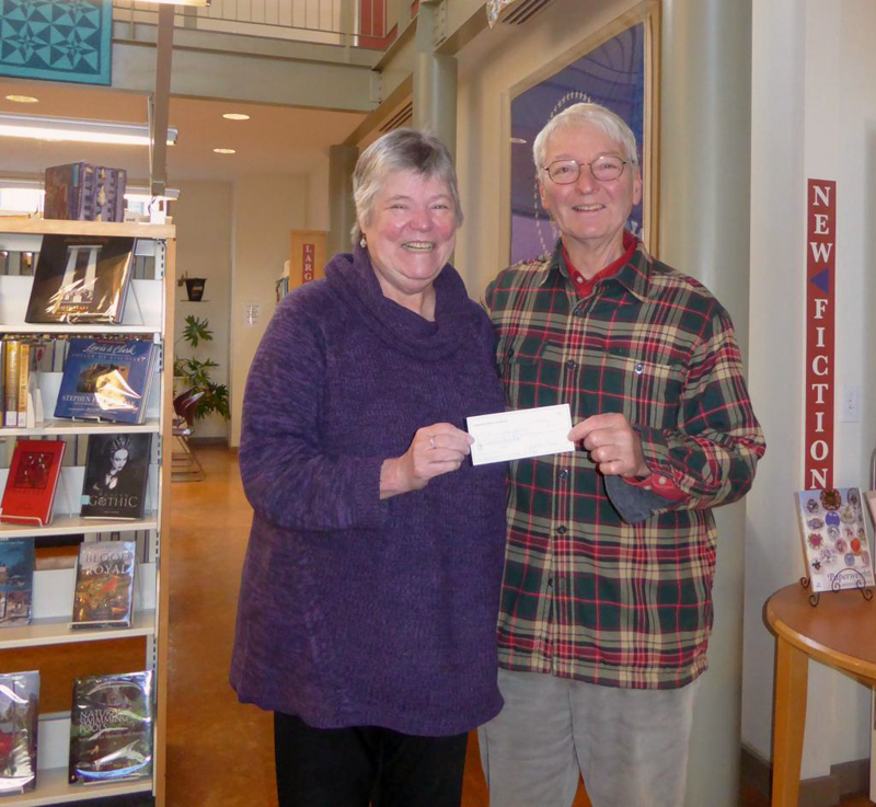 Skidompha Library Executive Director Pam Gormley receives a check for renewal of a museum pass to the Portland Museum of Art from Paul Sherman, vice president of the Pemaquid Group of Artists.