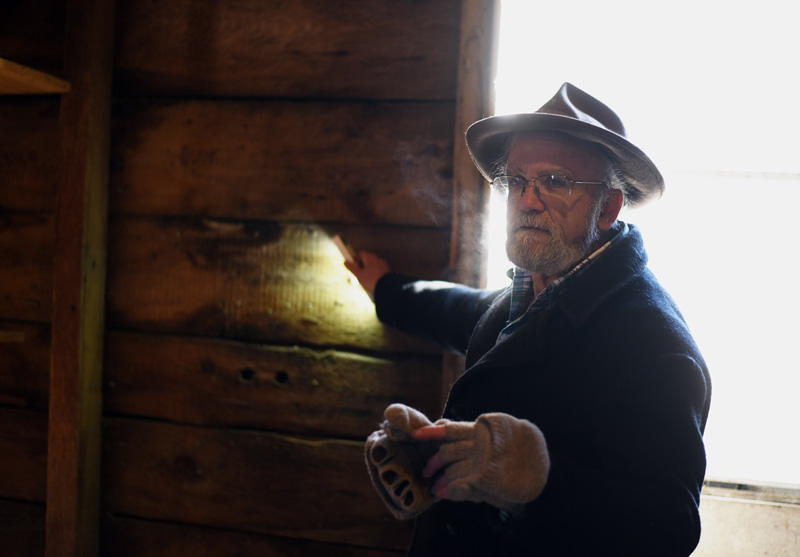 Phil Averill uses a flashlight to illuminate a wall of the old Pemaquid Mill during a tour Thursday, Jan. 17. The boards for the wall were cut with an up-and-down saw, he said. (Jessica Picard photo)