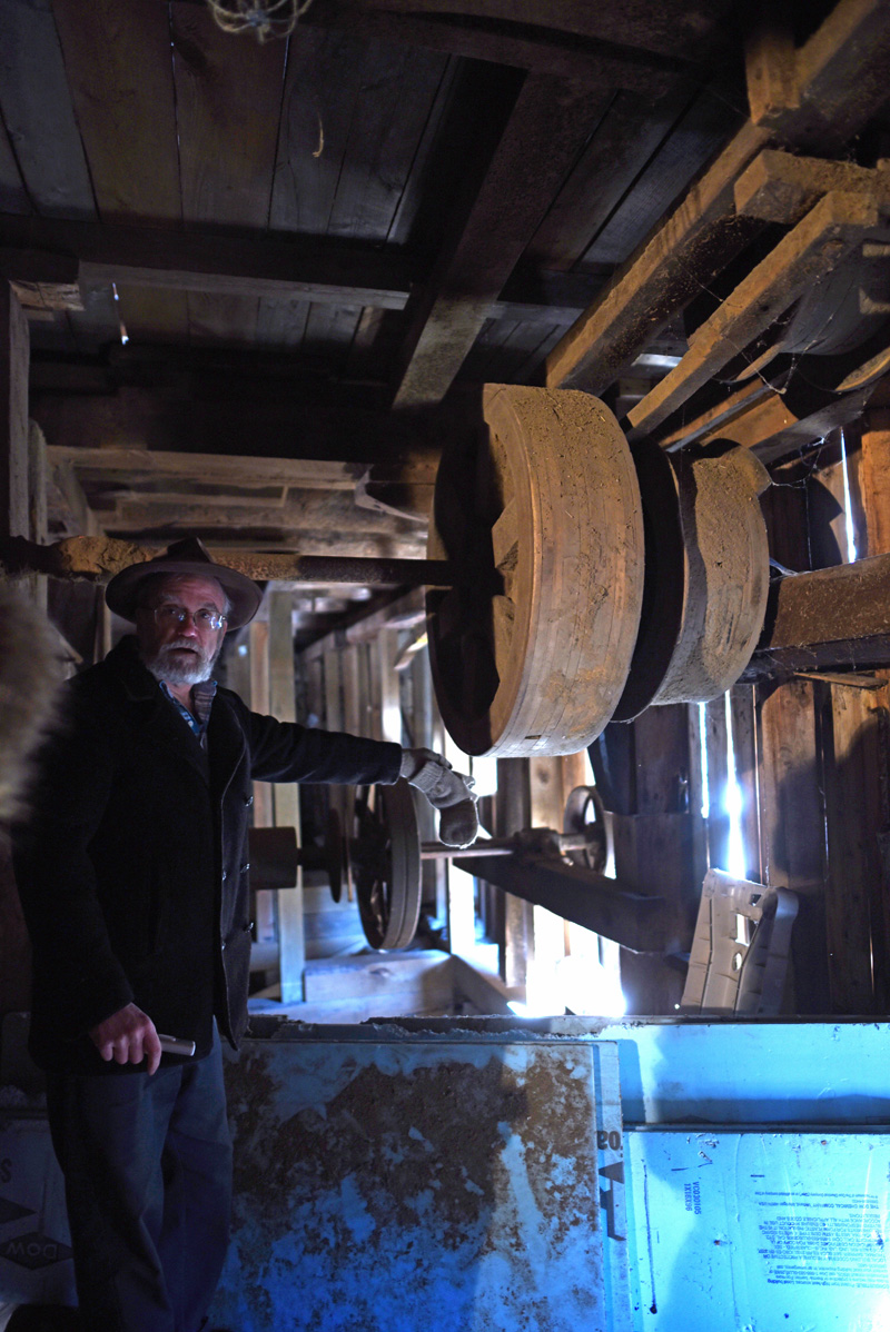 Phil Averill points out equipment in the basement of the mill. (Jessica Picard photo)