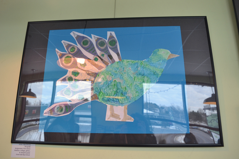 Damariscotta's upper Main Street streetscape is reflected in the glass covering a collage piece depicting a peacock created by GSB seventh-grader Mya Bessey. (Christine LaPado-Breglia photo)