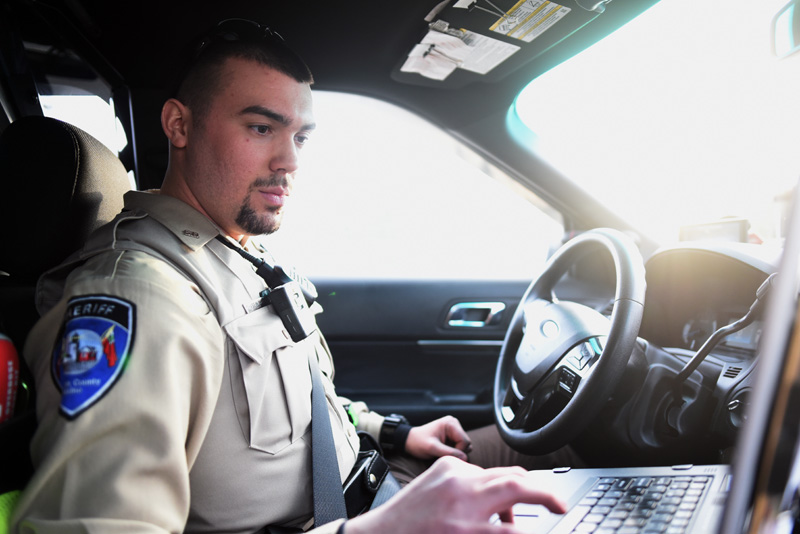 Lincoln County Sheriff's Deputy Chase Bosse works on the computer in his cruiser Thursday, Jan. 10. (Jessica Picard photo)