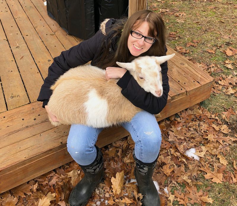 Megan McLaughlin sits on her back deck in Woolwich with one of her four goats, Campbell. McLaughlin will start work as the new county planner in February. (Photo courtesy Megan McLaughlin)