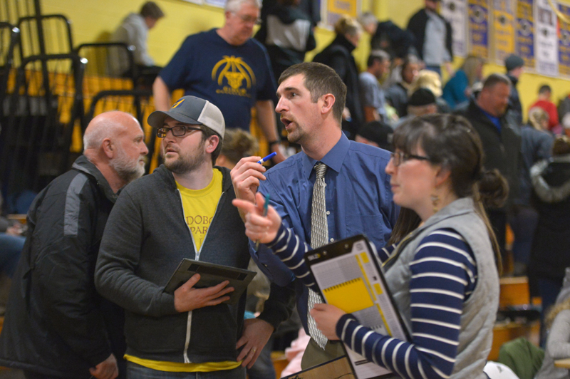 Medomak Valley girls basketball coach Ryan McNelly (center) confers with his brother, Lucas McNelly, at halftime of a home game against Gardiner on Dec. 28. (Paula Roberts photo)