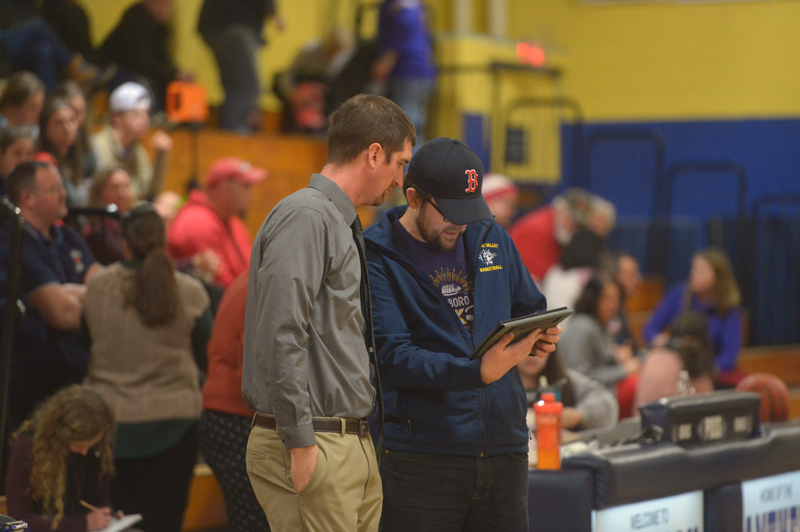 Medomak Valley High School girls varsity basketball coach Ryan McNelly and his brother, Lucas McNelly, review statistics from a recent home game. (Paula Roberts photo)