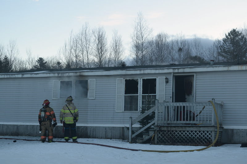 Firefighters look on as smoke drifts from the window of a mobile home fire at 139 Sheepscot Road in Wiscasset the morning of Wednesday, Jan. 16. (Jessica Clifford photo)