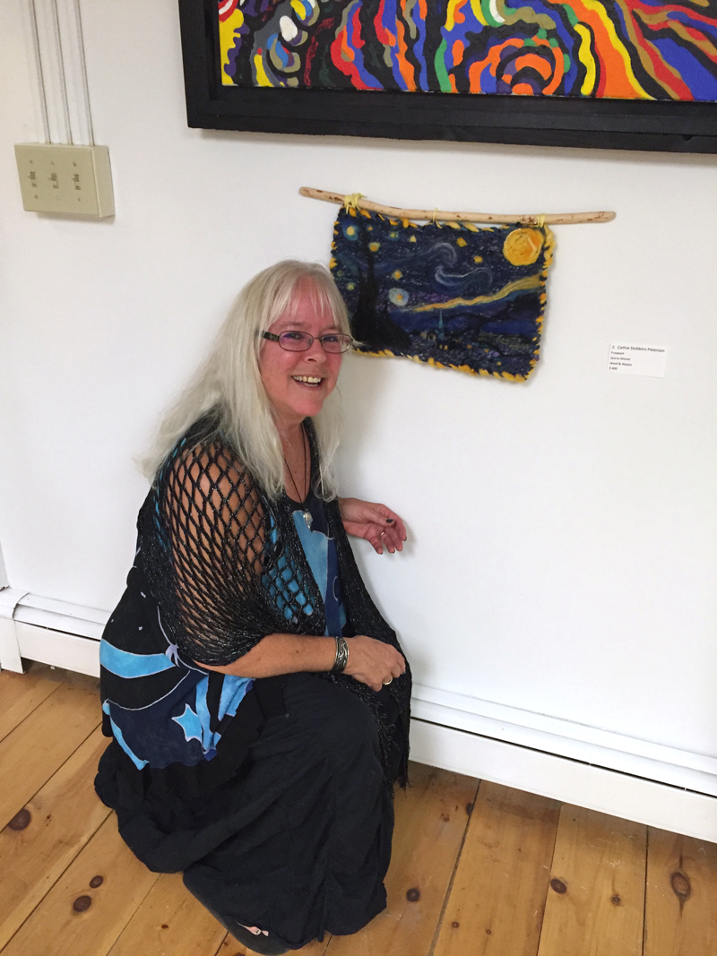 "Cathie Stebbins Peterson and her ""Starry Night"" wall hanging inspired by Vincent van Gogh's iconic painting ""The Starry Night."" It is unframed and hangs from a  ""beaver stick,"" as Peterson calls it."