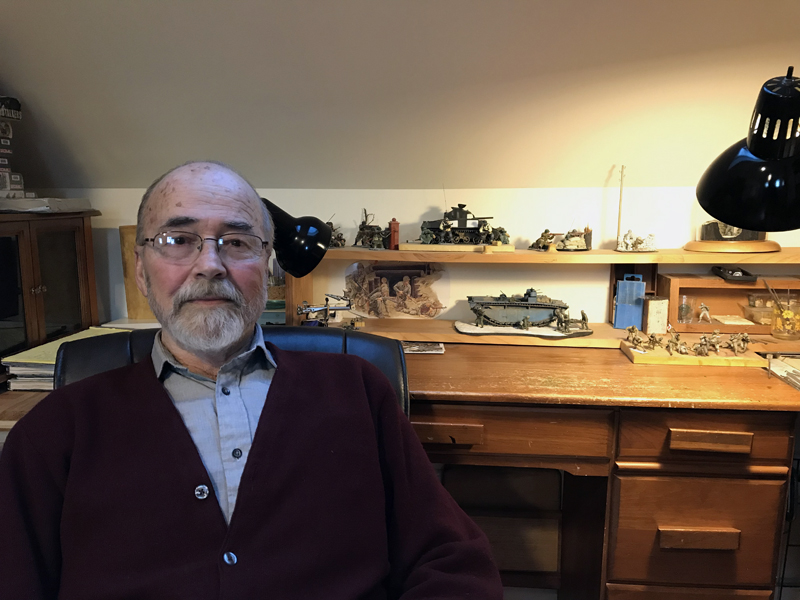 Ed Strausberg sits next to parts of an incomplete diorama of Saipan on his desk at his home in Round Pond. Unable to complete the work due to a tremor, he hopes to find someone willing to finish the job. (J.W. Oliver photo)
