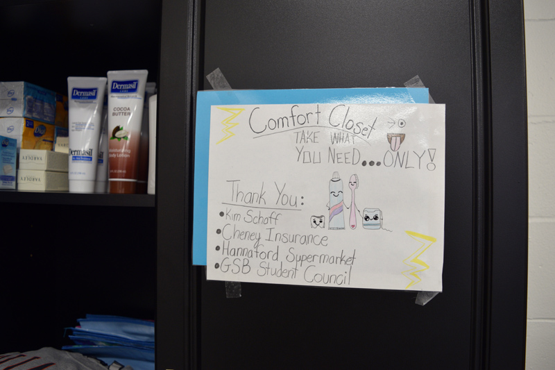 A sign on the door of the comfort closet invites students to take what they need and lists sponsors and supporters of the project. (Jessica Clifford photo)